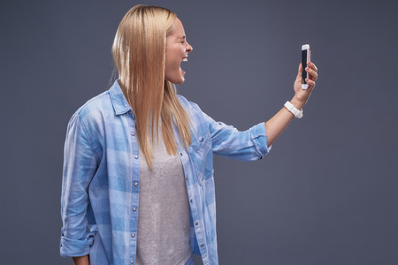 Waist up portrait of stressed blond girl holding smartphone and shouting at it. Isolated on blue-gray background 写真素材
