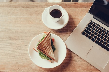 Top view photo of netbook, sandvich and black coffee in cup on wooden desk in restaurant