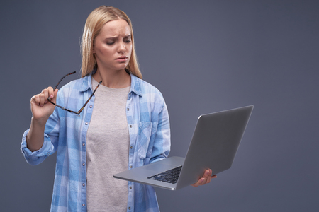 Waist up portrait of beautiful blond girl holding glasses and looking at laptop with confused expression Imagens