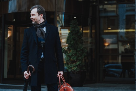 Focus on elegant man wearing classic clothes and carrying gripsack and umbrella. He is walking out of modern urban building and looking aside. Copy space in right side Фото со стока