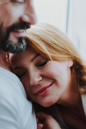Happy to be with you. Close up of happy smiling woman closing eyes and being embraced by her husband near window 스톡 콘텐츠