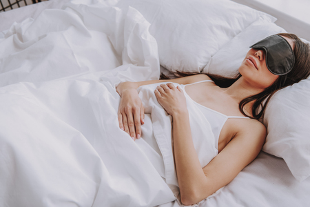 High angle of happy young lady with sleep mask covering up with soft blanket while lying in bedroom at home. Concept of rest Фото со стока - 116729458