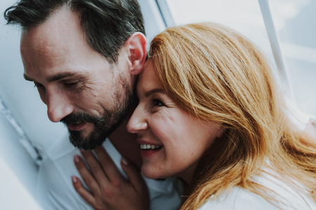 Happy to be with you. Close up of happy smiling woman tenderly embraced by her husband near window and enjoying time together