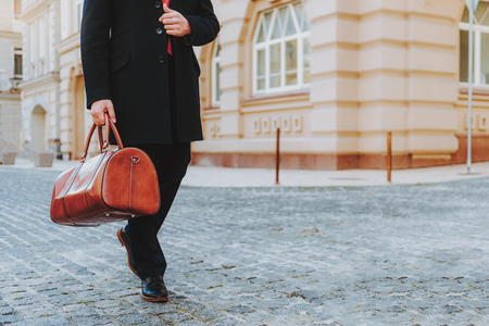 Focus on businessman in formal wear going along urban street. He is carrying elegant handbag. Copy space in right side Stock Photo