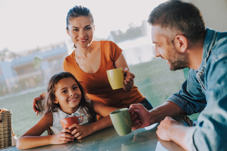 Pleasant nice couple resting with their little daughter at home while drinking tea