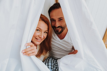 Happy to be with you. Close up portrait of beloved smiling woman and man tenderly embracing and looking out wigwam while enjoying time together
