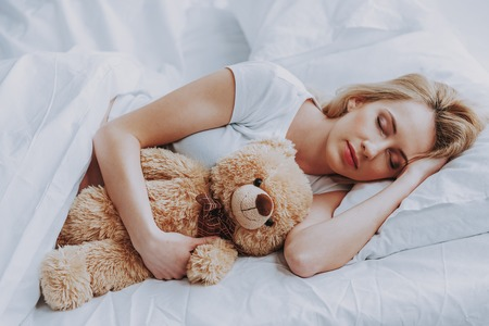 Happy pregnancy. Charming pregnant woman resting on bed at home while hugging teddy bear