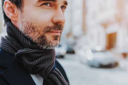 Focus on close-up profile portrait of bearded tranquil male in trendy scarf. He is standing in urban atmosphere and looking ahead. Copy space in right side