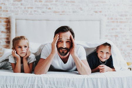 Family relationship concept. Close up portrait of smiling bearded father having fun on bed with children while his son covered by blanket Stock Photo