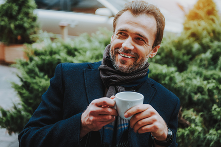 Focus on cheerful man laughing while enjoying cup of hot beverage. He is spending nice time in open air