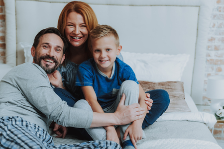 Close family relationship. Portrait of smiling happy mother and father embracing their little son while sitting on bed and spending weekend together