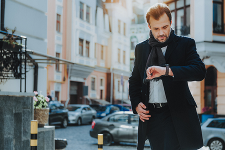 Focus on concentrated elegant male walking in urban street. He is looking at his watch and checking time. Copy space in left side Stock Photo