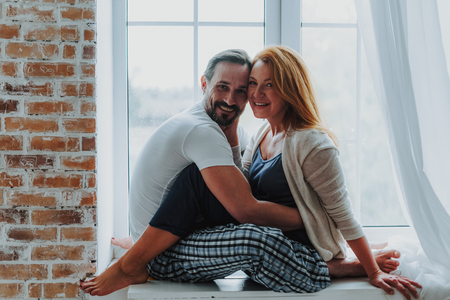 Happy to be with you. Side on full length portrait of happy smiling married man and woman embracing on window sill and looking on camera