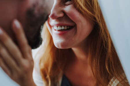 Happy to be with you. Close up of happy smiling woman and bearded man embracing and wanting to kiss Stock Photo
