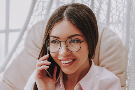Close up photo of clever young businesswoman expressing happiness while speaking by cellphone. She is having chat in soft comfortable chair. Modern digital technology concept Stock Photo
