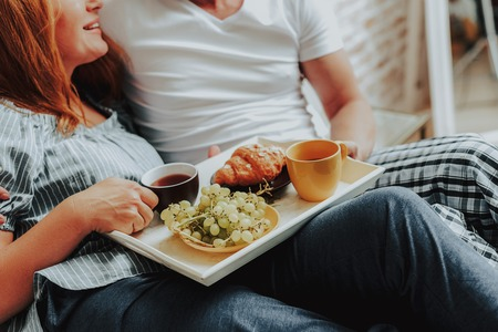Family relationship concept. Cropped head portrait of happy wife and husband laying in bed and having breakfast together Stock Photo