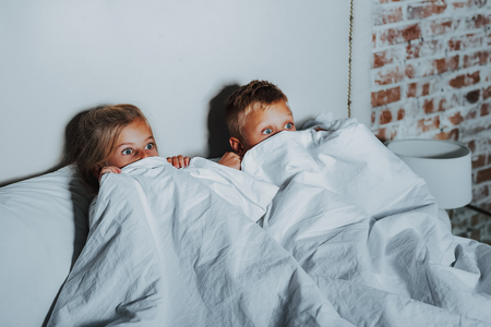 Horror movie. Waist up of scared little brother and sister hiding under white blanket while watching terrible movie on television at home