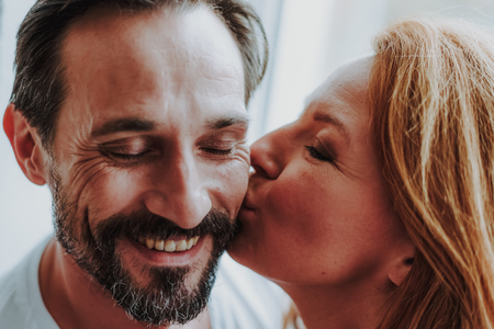 Close up of happy smiling wife tenderly kissing her husband near window and enjoying time together Reklamní fotografie