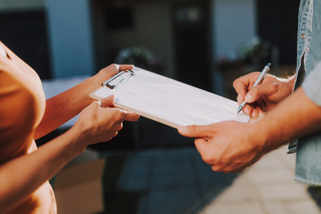 Close up of a folder in hands of a professional courier holding it while getting a signature of the client Reklamní fotografie