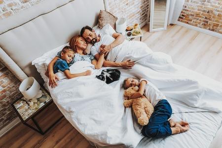 Geliebtes Spielzeugkonzept. Draufsichtporträt von Eltern mit Sohn und Katze, die zusammen schlafen und kleine Tochter, die mit Teddybär in der Hand tiefer auf dem Bett liegt