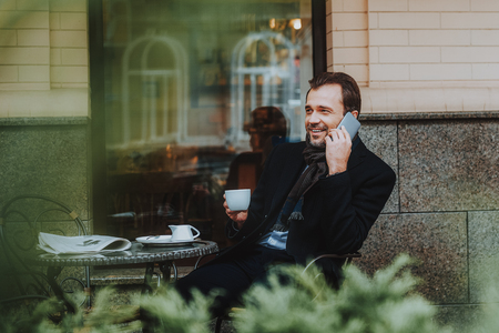 Focus on cheerful elegant male sitting in restaurant outdoors. He is chatting on cell phone while having hot drink and reading newspaper