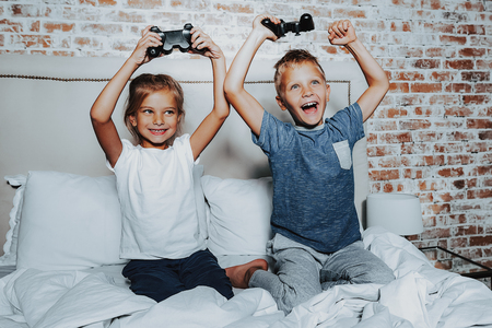Who is the winner in competition. Portrait of happy fair haired brother and sister being very joyful after finishing of playing with game console together