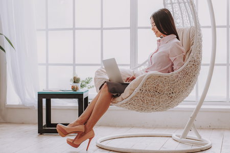 Full length of charming asian lady sitting near wide window on design chair with digital device. She is working in cozy room. Copy space in left side Standard-Bild