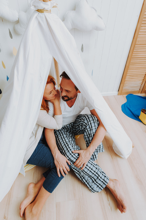 Happy to be with you. Top angle portrait of beloved smiling woman and man tenderly embracing while sitting in wigwam and enjoying time together Stock Photo