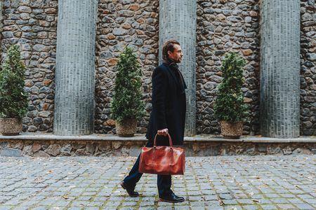 Full length profile portrait of stylish man standing in old street in city. He is wearing classic clothes and carrying handbag. Copy space in left side