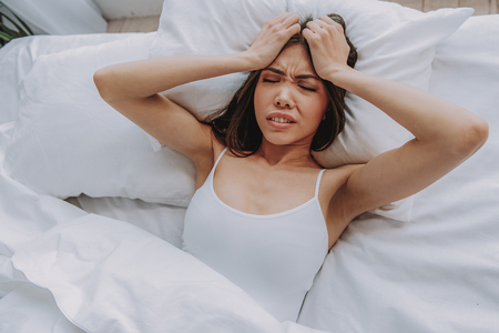 Bad beginning of new day. Top view portrait of asian woman suffering from headache while lying in bed at home Stock Photo