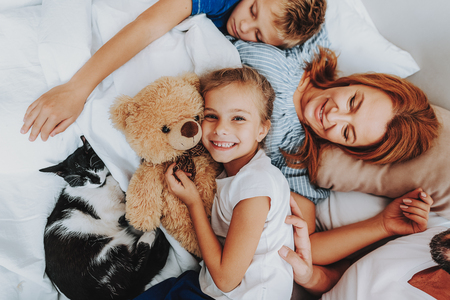 Lazy morning in bed. Top view close up of happy smiling little girl laying with parents and cat on bed while her brother sleeping next to mother Stock Photo