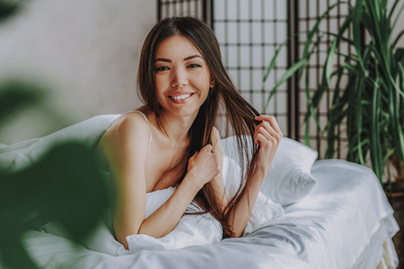 Portrait of happy asian woman touching her hair while lying in bed. Relaxation concept