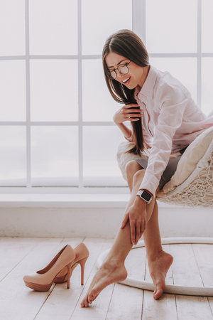 Working hours are over. Tired asian lady expressing leg pain while sitting on soft chair near shoes Stock Photo