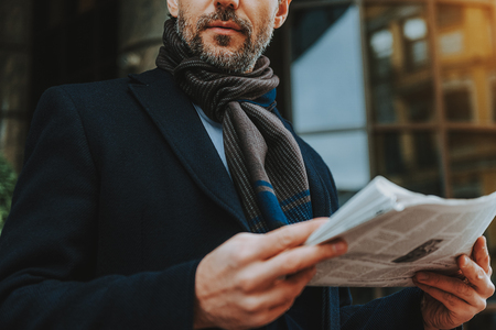 Focus on elegant man standing outdoors. He is reading paper while being well-dressed Stok Fotoğraf - 116739356