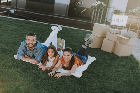 Cheerful friendly family happy to sell their house while enjoying time in the yard
