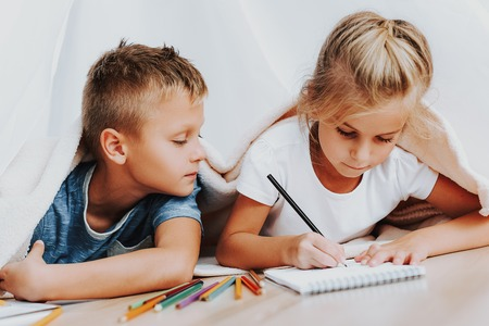 Family relationship concept. Close up portrait of elder brother looking how his sister drawing with colorful pencils in notebook while they covering by blanket