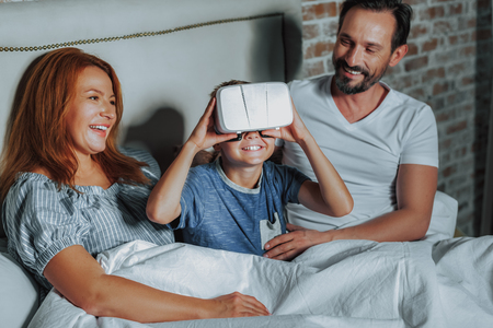 Family spending time. Waist up portrait of smiling little boy with virtual reality headset watching something interesting being together with parents in bed Imagens - 116732498