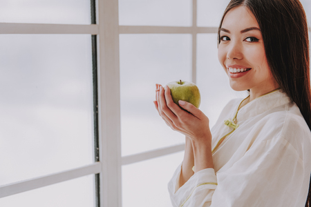 Portrait of pretty asian woman tasting delicious apple. Health concept. Copy space in left side