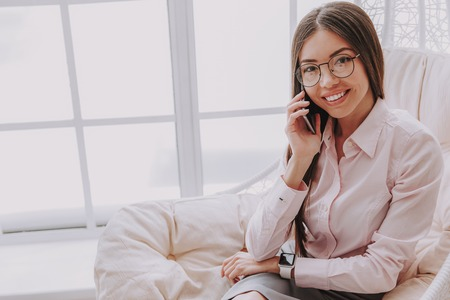 Half length photo of happy smart woman speaking by cellphone while sitting on comfortable chair. Copy space in left side Stock Photo