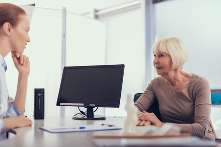 Focus on mature lady sitting on chair during appointment with doctor. Female expert is listening to complaints while being opposite at table with personal computer Stockfoto