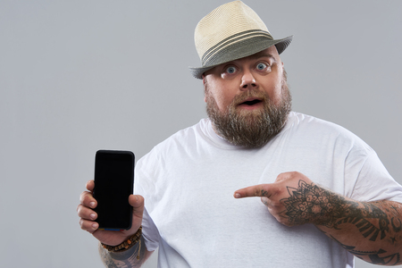 Bearded fat man in the hat standing isolated on the grey background and opening his mouth while pointing to the screen of his modern gadget