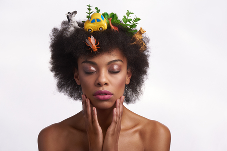 Fashion look and human nature. Close up portrait of peaceful afro american woman in safari hairstyle closing eyes while tenderly touch her face. Isolated on white