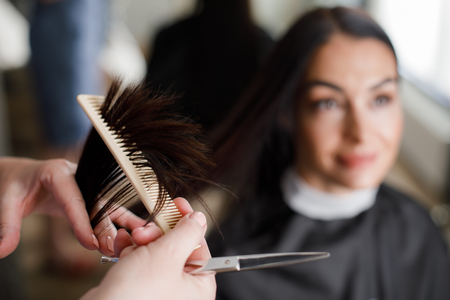 Focus on close-up of stylist hands combing female hair. She is holding scissors for cutting split ends while smiling customer is sitting in chair