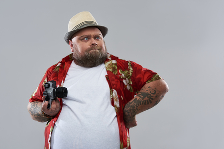 Waist up isolated on grey background photo of tourist in Hawaiian shirt holding retro camera and frowning while looking into distance