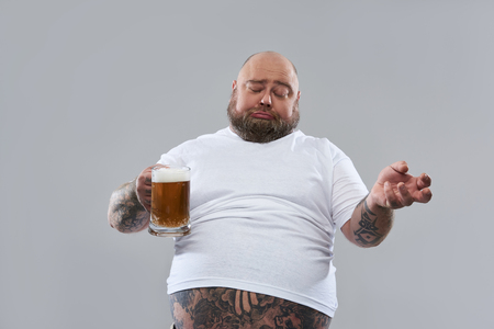Waist up of fat lazy man closing his eyes while being drunk and holding a glass of beer while being isolated on the grey background