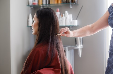 Woman is sitting in chair and wearing protective gown during treatment procedures in beauty salon. Stylist is standing behind and straightening her long hair with comb