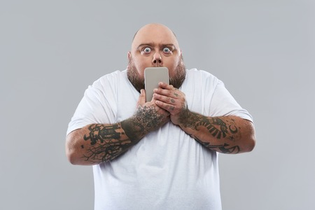 Waist up of funny fat tattooed man standing isolated on the grey background and opening his eyes wide while expressing surprise and holding smartphone