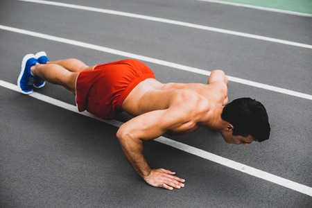Full length side view concentrated stripped to waist young man doing push-ups. Sport concept