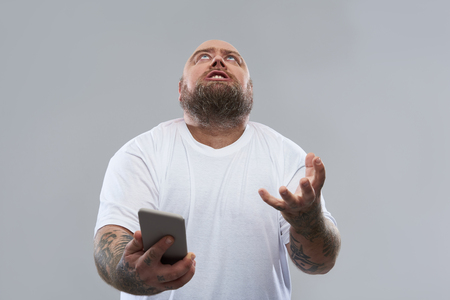 Bearded fat tattooed man in white T-shirt standing isolated on the grey background and putting his head and hand up