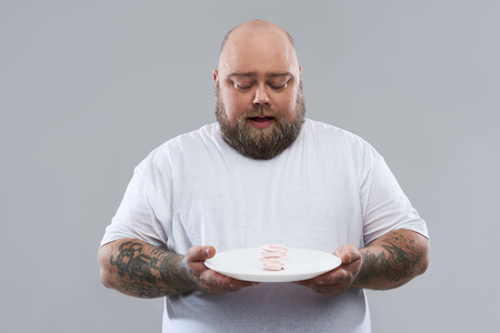 Waist up of fat bearded man in white T-shirt standing against the grey background and carefully holding big plate with marshmallow souffle on it
